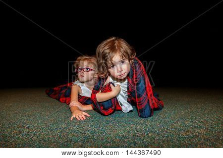 Two flower girls lay on the floor in a blanket at the end of a busy wedding day after the reception. The youngest crawls toward the camera with a sad look and messy face.