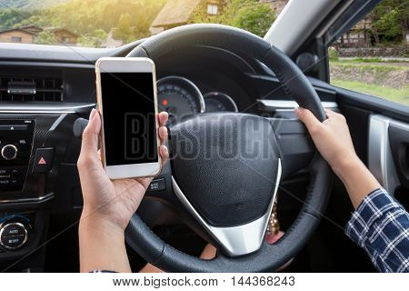 Young woman driver using touch screen smartphone and hand holding steering wheel in a car with japanese traditional (Shirakawa-go) village background