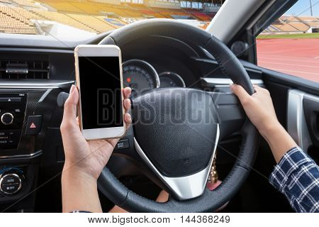 Young woman driver using touch screen smartphone and hand holding steering wheel in a car with football or soccer stadium background
