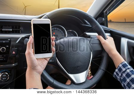 Young woman driver using touch screen smartphone and hand holding steering wheel in a car with wind turbine at sunset background