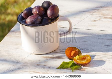 Heap Of Plums In Metallic Mug On Wooden Table In Garden On Sunny Day