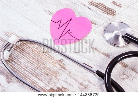 Heart Of Paper With Cardiogram Line And Stethoscope On Wooden Background, Medicine And Healthcare Co
