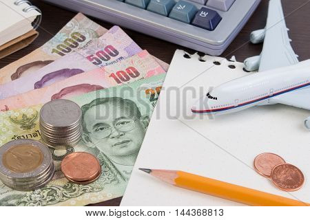 Thai Passport with Thai money banknote Thai coin and airplane. The passport of Thai citizen and Thai banknote on white background.