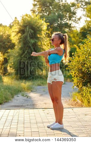 Young slim woman doing stretching humeral girdle in a city park. Outdoors Sports. Healthy lifestyle concept. Morning exercises