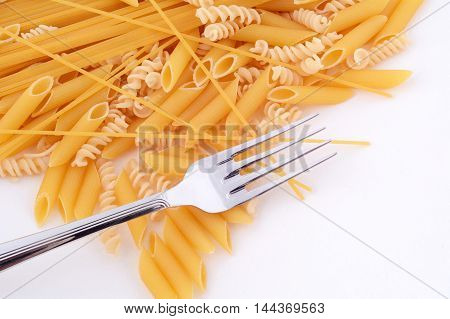 Various types of pasta and fork isolated on white background