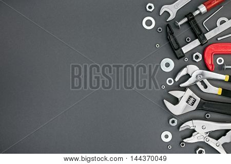 Set Of Different Adjustable Wrenches And Clamps On Grey Table