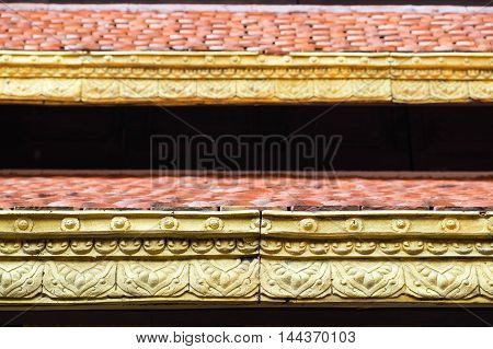 Close up detail of Thai style roof with orange and gold color for background and texture.