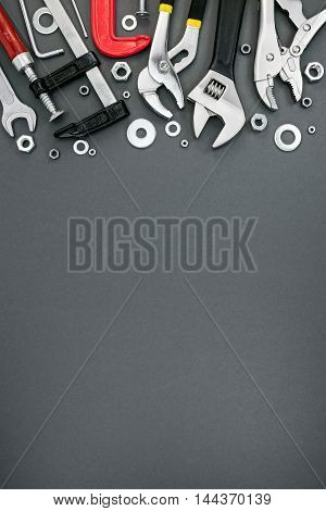 Various Clamps And Adjustable Wrenches On Grey Background