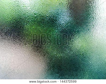 Window glass with condensation on garden blur background