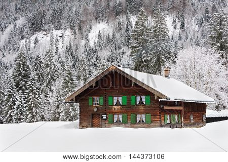 Wooden traditional Bavarian style log cabin house with green shutters in a forest in the snow in winter in Bavaria at the border between Germany and Austria.