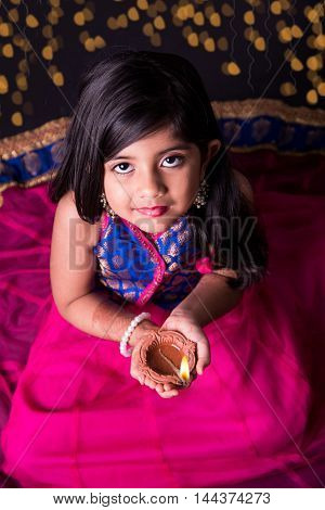 greeting card showing indian small Girl holding a diya on diwali festival, asian girl and diya, over black background