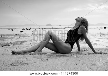 Black and white photo of elegant blonde pretty woman with wet look wearing black swimsuit lying on the sandy beach near the sea over sky background
