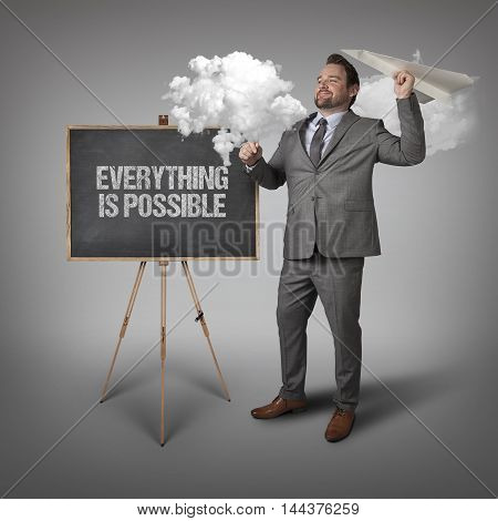 Everything is possible text on blackboard with businessman and paper plane