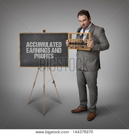 Accumulated Earnings and Profits text on blackboard with businessman and abacus