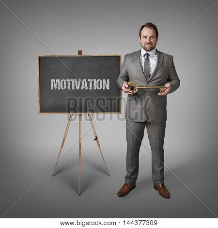 motivation text on  blackboard with businessman and key