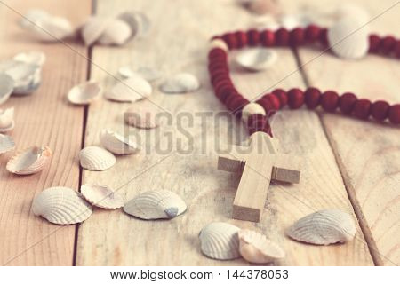 the rosary, shells, stones on the wooden background; toned photo