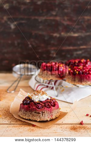 Gluten free homemade cakes with fresh cranberry, whipped cream, lemon zest and cinnamon on top on a wooden table and on the cooling rack, selective focus