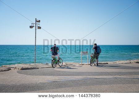 TEL AVIV, ISRAEL - JUNE 4, 2015: Two tourists on rented bikes in Tel Aviv