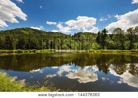Beautiful view mirror on the water surface of a pond in the valley Pilske udoli Boskovice. Moravian landscape.