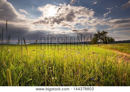Sun rays shining through the clouds on the meadow. Moravian landscape Okrouhla.