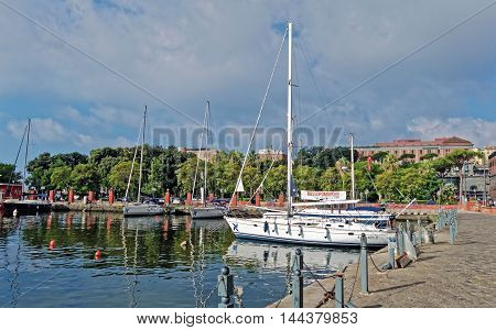 NAPLES, ITALY - AUGUST 5, 2016: Panoramic summer cityscape of boats and yachts moored at the Molosiglio pier near the Molosiglio gardens and the maritime station of Naples, Italy