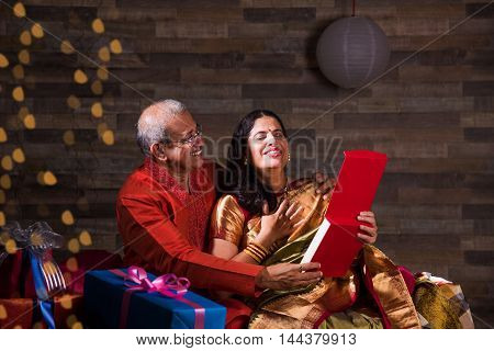 senior indian man presenting woman necklace as gift in diwali, Indian man gifting necklace to his wife
