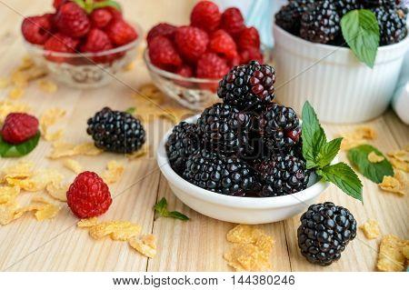 Freshly picked blackberries and raspberries on a light wooden background