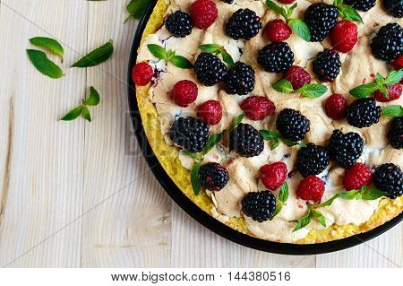 Pie (Tart) with fresh blackberries and raspberries air meringue decorative mint. Close up. The top view