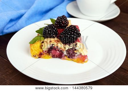 A piece of the pie (Tart) with fresh blackberries and raspberries air meringue mint decoration on a white plate