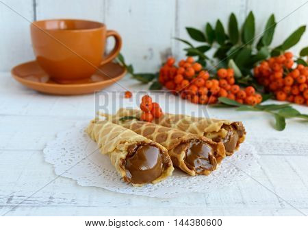 Homemade honey wafers rolled into a cone filled with caramel (condensed milk) a cup of tea rowan berries on a white background. Close up