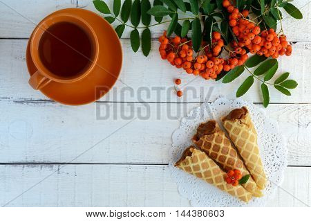 Homemade honey wafers rolled into a cone filled with caramel (condensed milk) a cup of tea rowan berries on a white background. top view