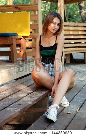 Cute sporty young woman wearing shorts black tee top and sneakers holding backpack posing in the cabin outside in summer
