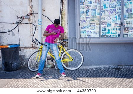 TEL AVIV, ISRAEL - JUNE 5, 2015: Man on a bicycle looking at the phone in the old city of Tel Aviv. June 5, 2015. Tel Aviv, Israel.