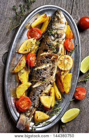 Roasted fish with baked potato wedges top view