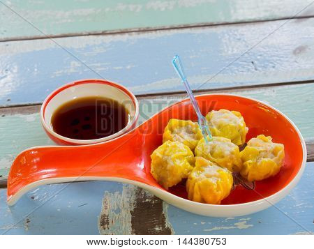 Shrimp dim sum with sweet sauce on a plate . on Wood table .