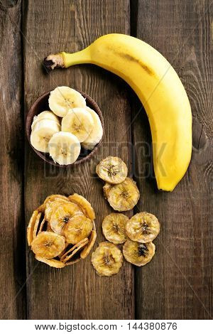 Fresh bananas and chips on wooden table top view