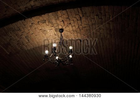 Vintage chandelier at the ceiling of a cellar