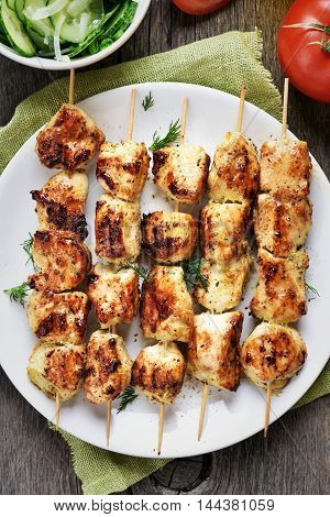 Grilled chicken meat on bamboo skewers top view