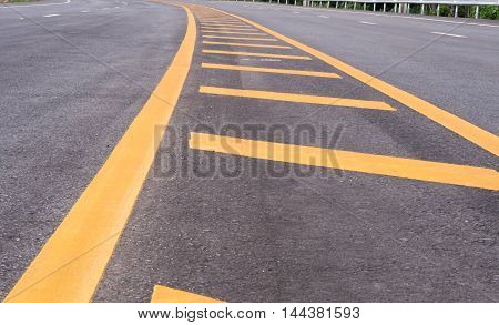 The curve  Road  and the yellow traffic lines.