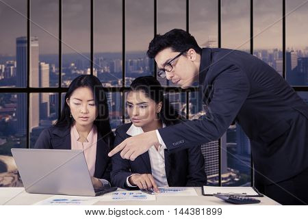 Group of multi ethnic business team making job plans together with paperwork and laptop in office