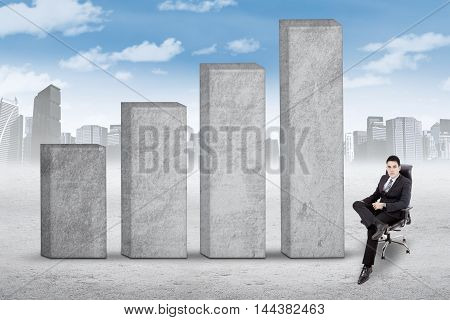 Successful businessman wearing formal suit and sitting on the office chair near the business graph