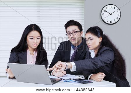 Three multiracial entrepreneurs looks busy while discussing in the office with laptop computer on table