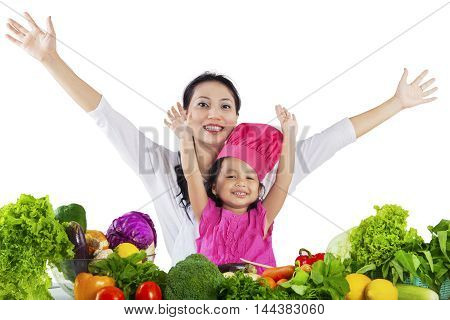 Portrait of cheerful mother and her daughter raise hands with fresh vegetables on the table