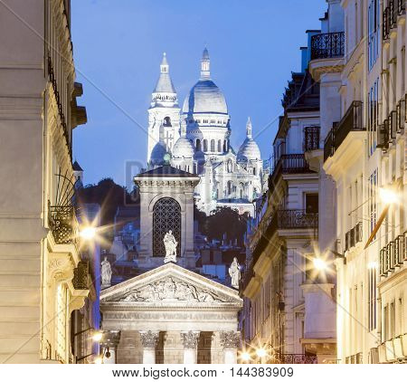 The church Notre Dame de Lorette and basilica Sacre Coeur in the background at night Paris France.