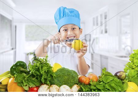 Cute little boy cutting a lemon with a knife while wearing a cooking hat with vegetables on the table shot in the kitchen