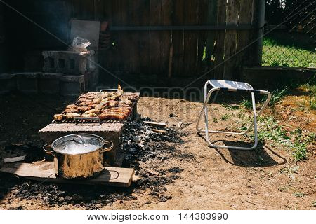 Backyard barbecue with sausages, burgers and chicken
