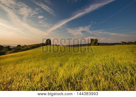 Sunrise and green meadow. In the distance misty hills. Moravian landscape Makov.