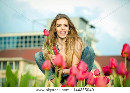 happy beautiful young slender girl is sitting with red tulips