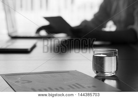 glass of water on conference table in conference room with morning light.
