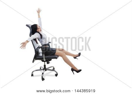 Photo of happy female entrepreneur celebrating her success while sitting on the office chair and raise hands